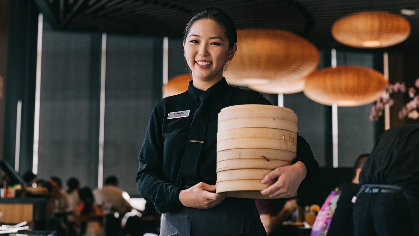 A server smiling and holding a bamboo basket of Xiao Long Baos.