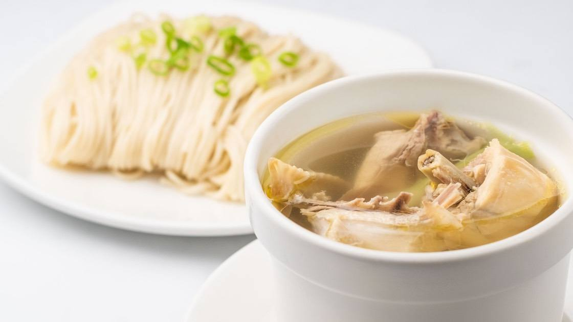 House Jidori Chicken Noodle Soup (Steamed) House Beef Noodle Soup (Steamed) in a white bowl and a plate of noodles, close up