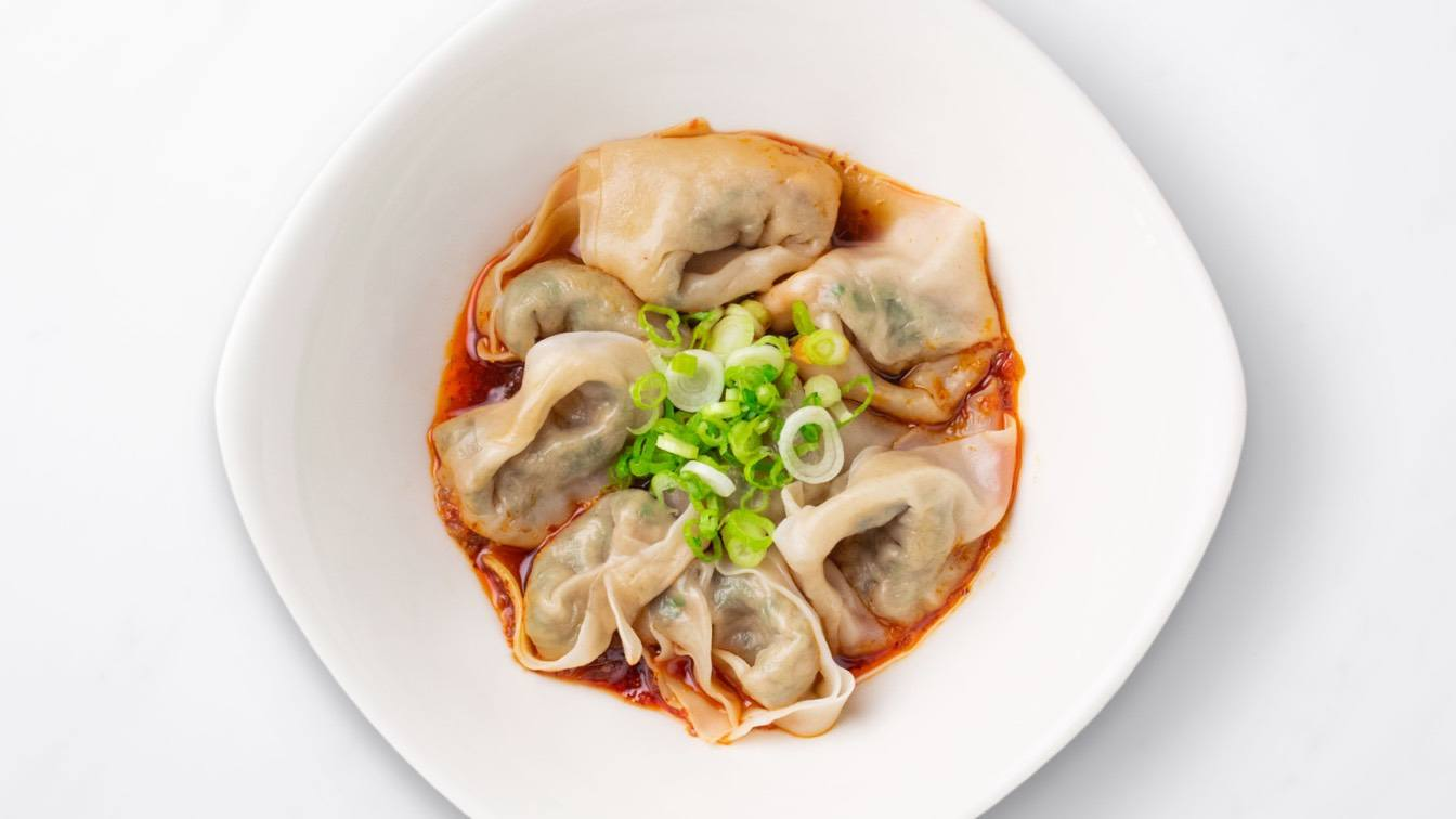 Vegetable & Kurobuta Pork Wontons with Spicy Sauce in a white bowl