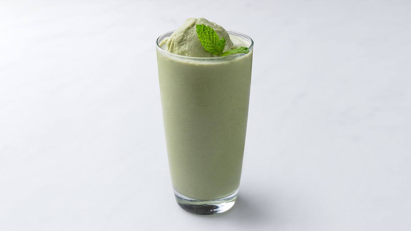 A photo of a matcha smoothie in a glass.