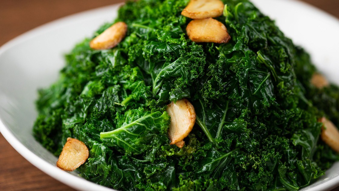Sauteed Kale with Garlic on a white plate, close up