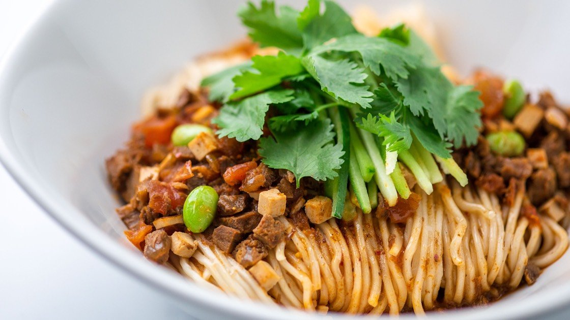 Noodles with Diced Beef & Szechuan Peppers in a white bowl, close up