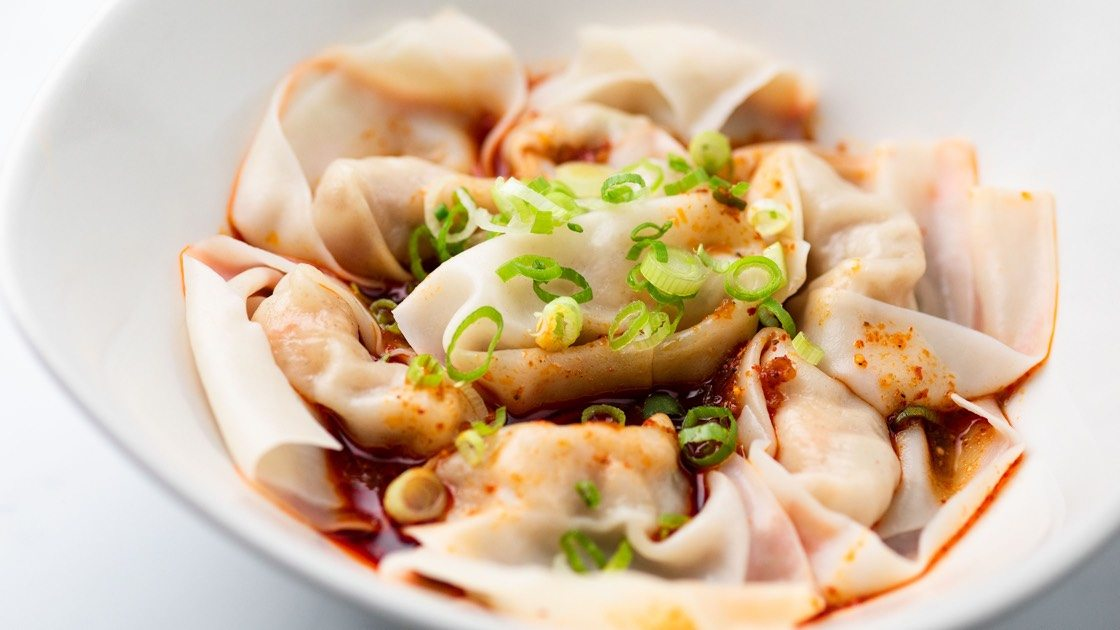 Shrimp & Kurobuta Pork Wontons with Spicy Sauce in a white bowl, close up