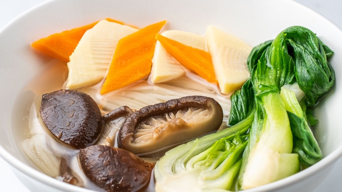 Vegetarian Noodle Soup with mushrooms in a white bowl, close up