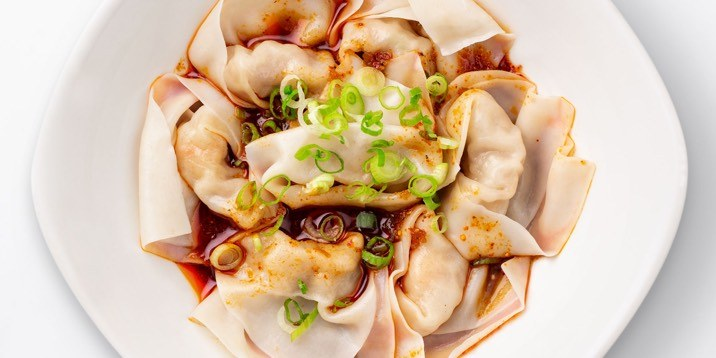 Shrimp & Kurobuta Pork Wontons with Spicy Sauce in a white bowl