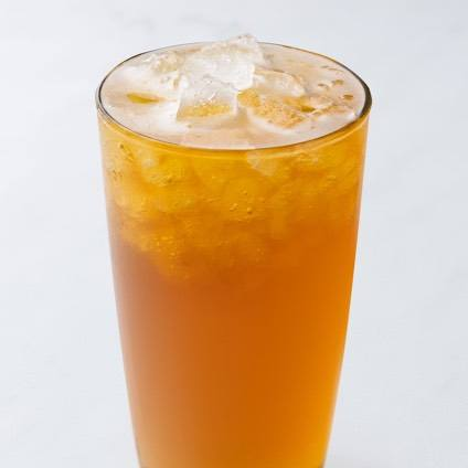 A photo of a fresh orange green tea in a glass.