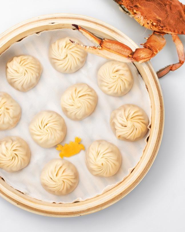 Crab leg over a basket of Crab & Kurobuta Pork Xiao Long Bao