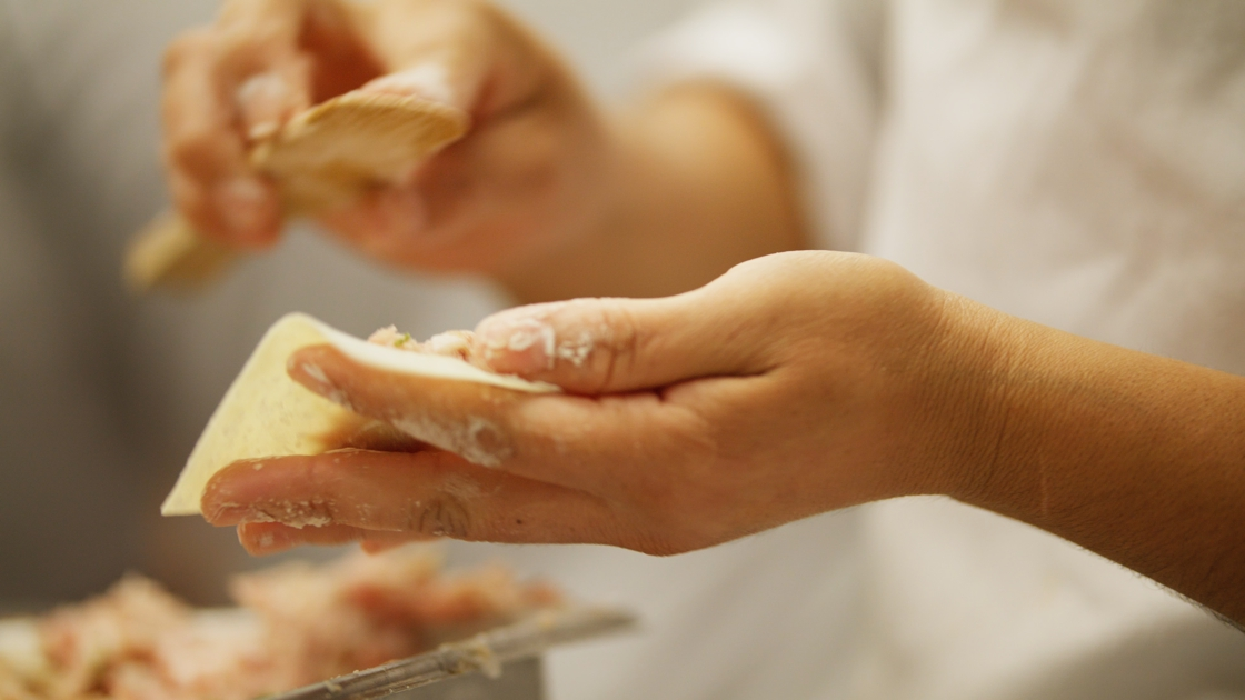 A chef folding wontons to be steamed.