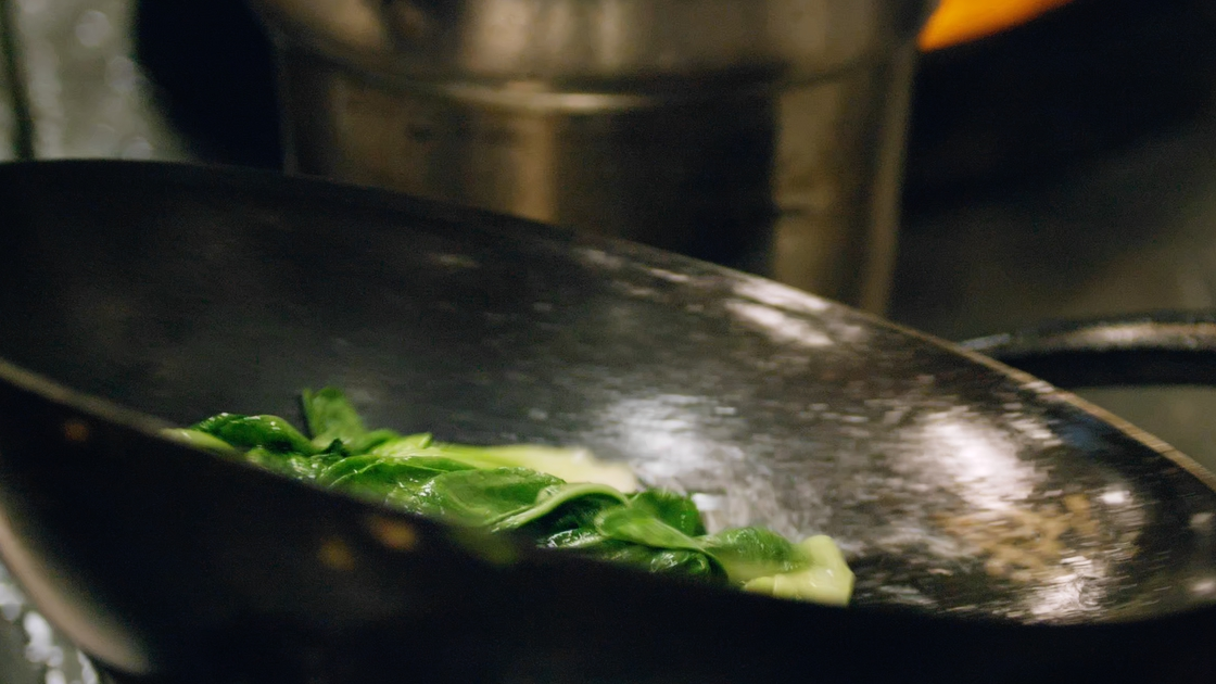 Bok choy being cooked in a pan.