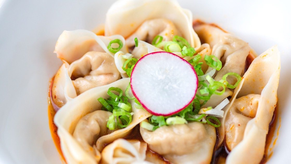 Jidori Chicken Wontons with Spicy Sauce in a white bowl, close up