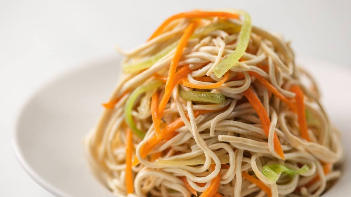Soy Noodle Salad in a white bowl, close up