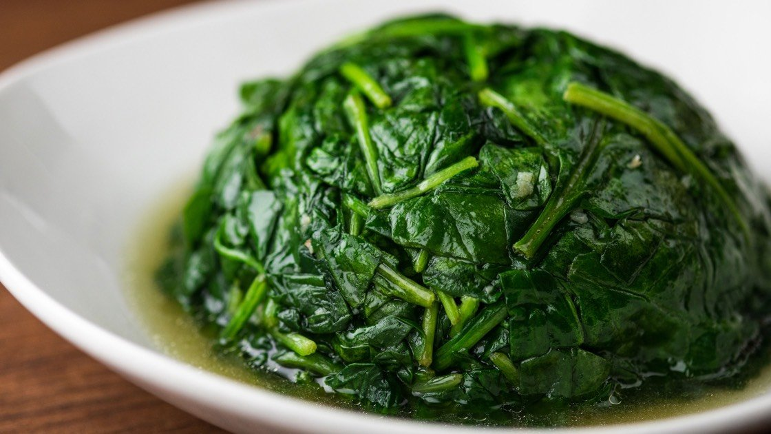 Round of sauteed Spinach with Garlic in a white dish, close up