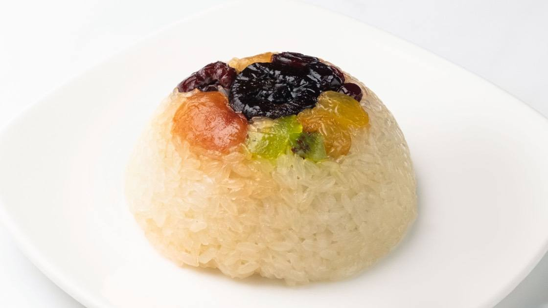 Eight-Treasure Sticky Rice on a white plate, close up