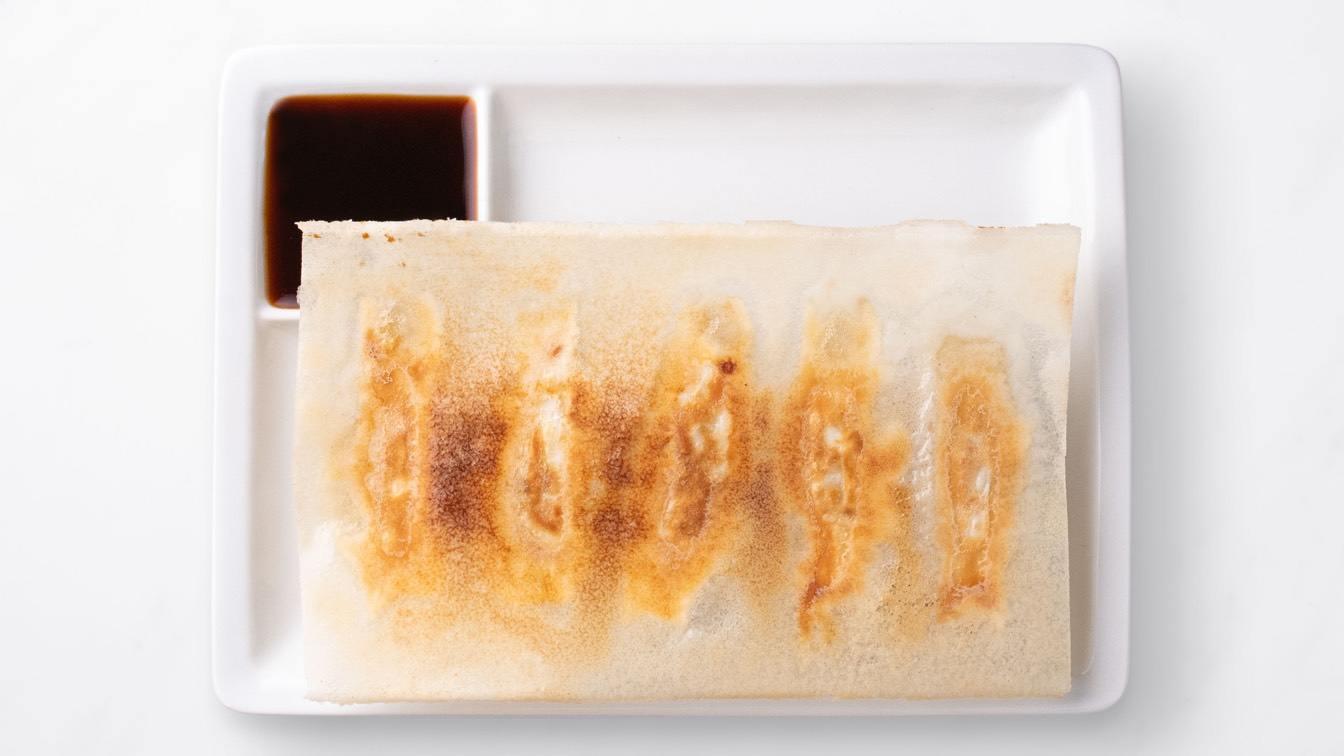 Shrimp & Kurobuta Pork Pot Stickers on a white plate with dipping sauce