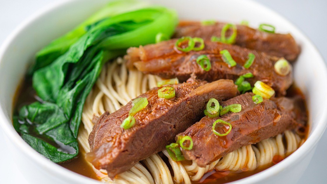 Braised Beef Noodle Soup in a white bowl, close up