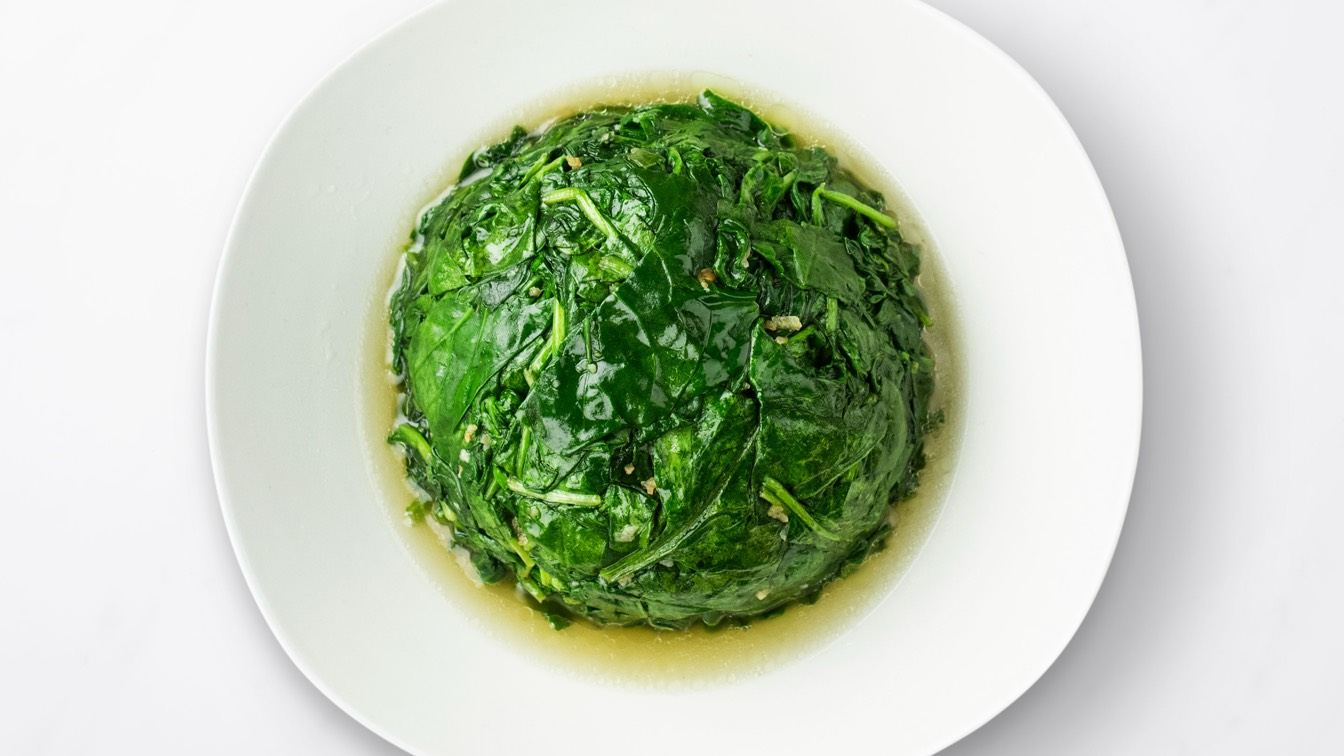 Round of sauteed Spinach with Garlic in a white dish