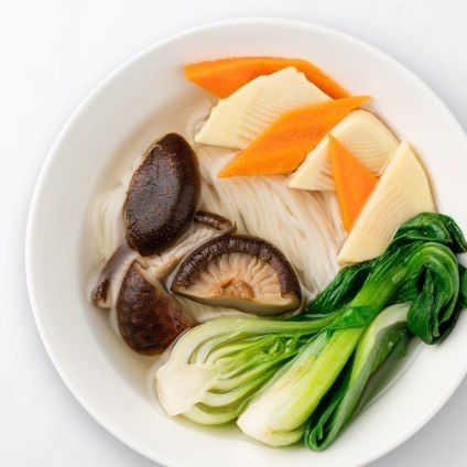 Vegetarian Noodle Soup with mushrooms in a white bowl