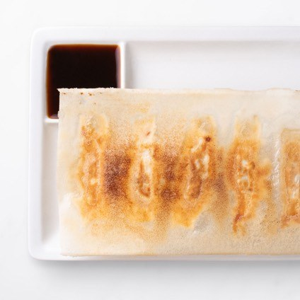 Shrimp & Kurobuta Pork Pot Stickers Shrimp & Kurobuta Pork Pot Stickers on a white plate with dipping sauce