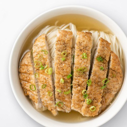 Sliced pork chop on top of  noodle soup in a white bowl