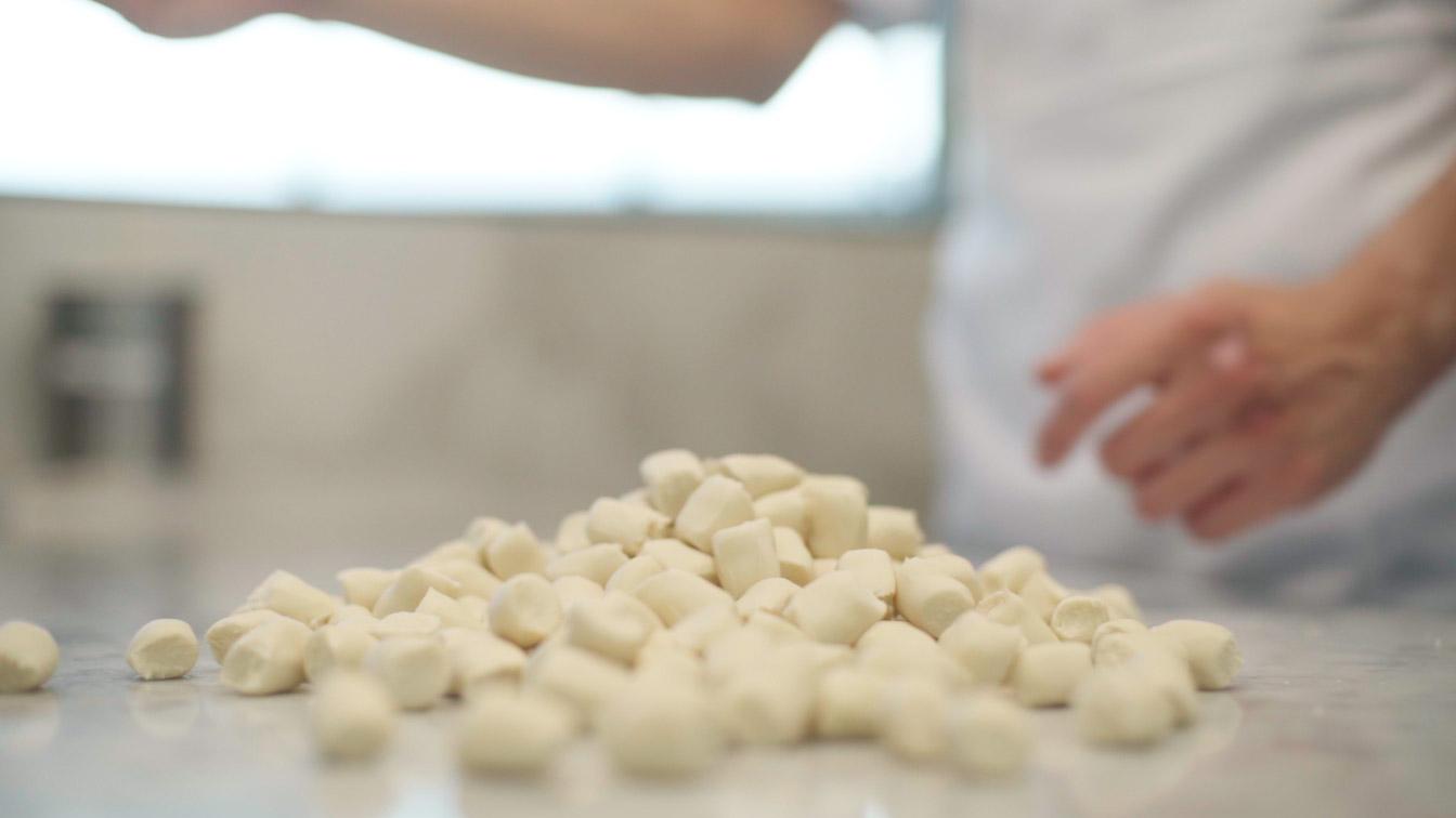 A chef adding flour to several dough balls.
