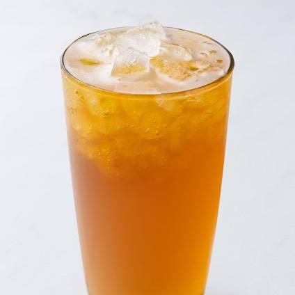 A photo of a fresh orange green tea in a glass.