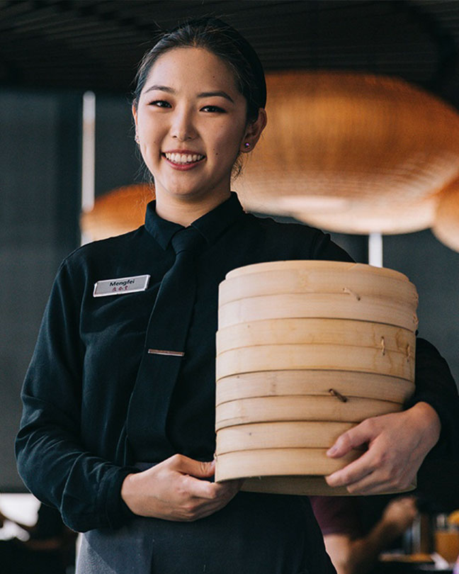 A waiter smiling and holding a bamboo basket of Xiao Long Baos.