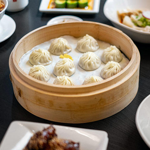 A family style meal featuring soup dumplings.