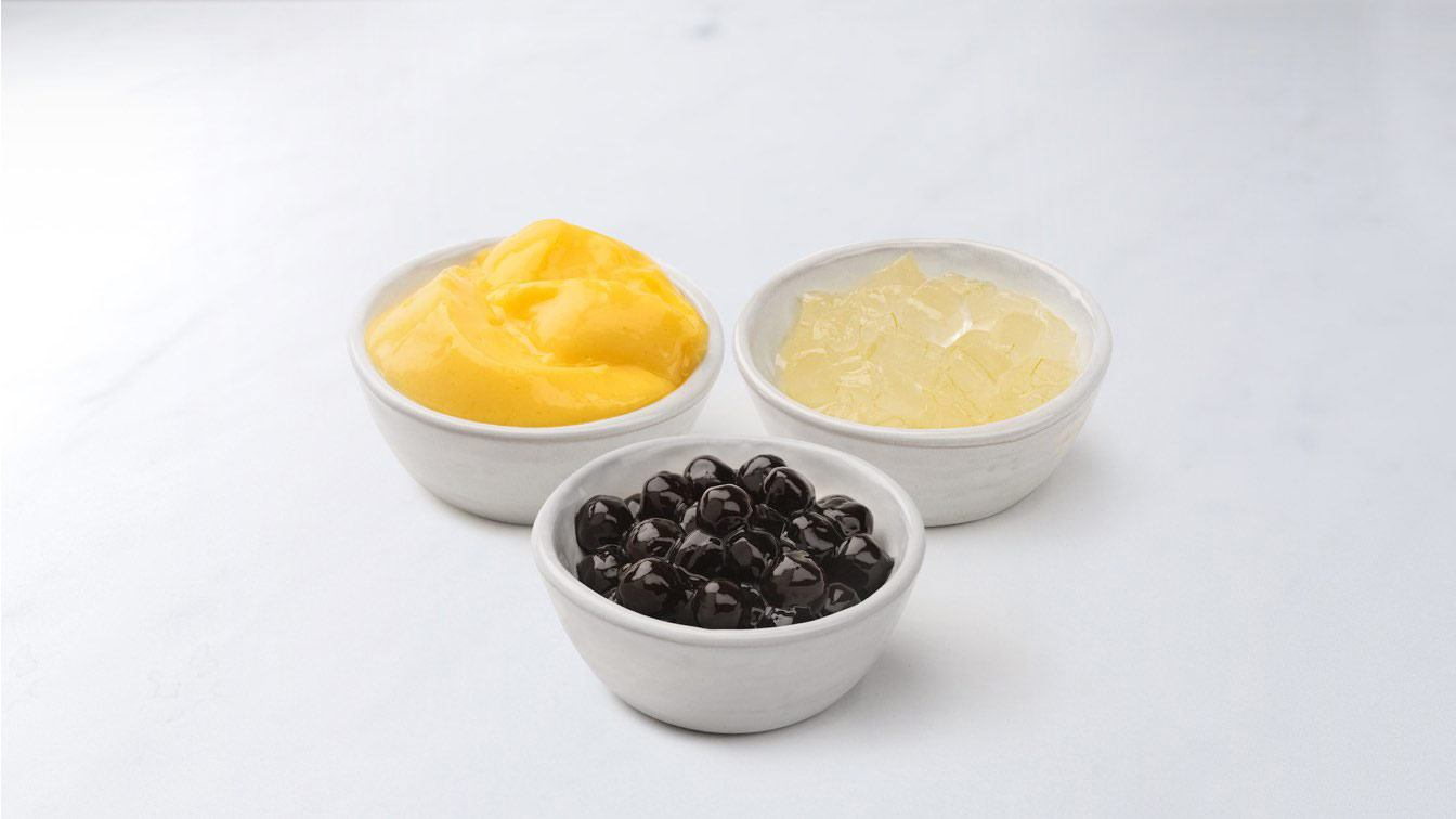 Three white bowls of drink add-ons: boba, aloe, and pudding.