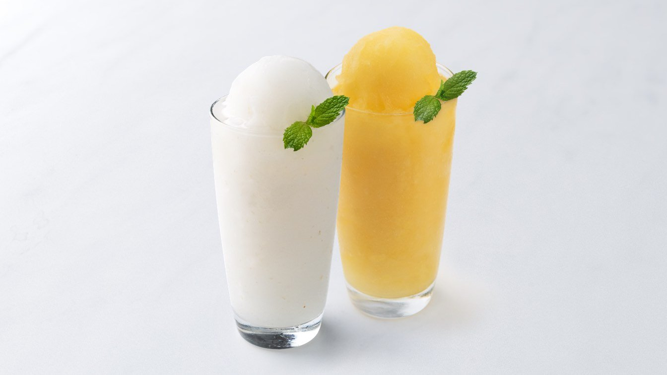 A photo of two glasses of lychee slush and mango slush side-by-side