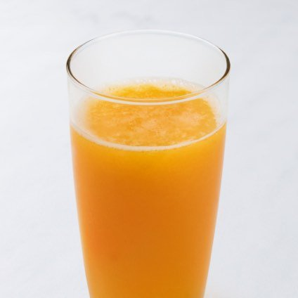 Glass of fresh squeezed OJ on white background