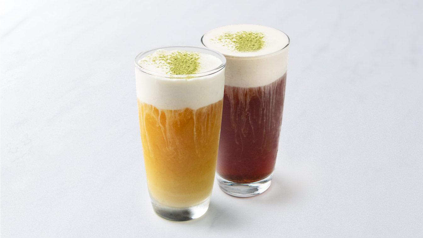 A photo of two sea salt cream-topped black and green teas in side-by-side glasses.