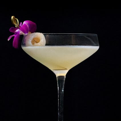 Three specialty cocktail drinks in martini glasses